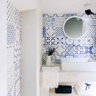 Design ideas for a mediterranean cloakroom in Other with multi-coloured tiles, ceramic tiles, multi-coloured walls, medium hardwood flooring, a trough sink and open cabinets.