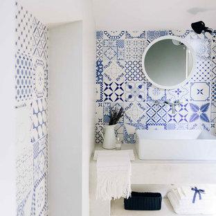 Пример оригинального дизайна: туалет в средиземноморском стиле с разноцветной плиткой, керамической плиткой, разноцветными стенами, паркетным полом среднего тона, раковиной с несколькими смесителями и открытыми фасадами