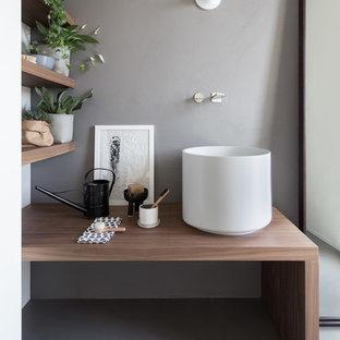 Idee per un bagno di servizio scandinavo con pareti grigie, lavabo a bacinella, top in legno, pavimento grigio e top marrone
