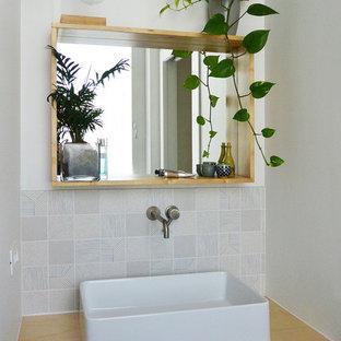 Ispirazione per un piccolo bagno di servizio nordico con WC a due pezzi, piastrelle bianche, piastrelle in ceramica, pareti bianche, pavimento in legno verniciato, lavabo a bacinella e top in legno