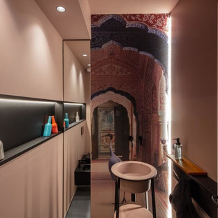 Design ideas for a medium sized modern cloakroom in Other with black cabinets, a two-piece toilet, grey tiles, pink walls, porcelain flooring, a pedestal sink, solid surface worktops and grey floors.