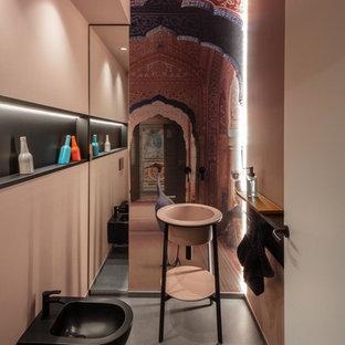 Foto på ett mellanstort funkis rosa toalett, med svarta skåp, en toalettstol med separat cisternkåpa, grå kakel, rosa väggar, klinkergolv i porslin, ett piedestal handfat, bänkskiva i akrylsten och grått golv