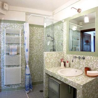 Idées déco pour un WC et toilettes campagne avec un WC suspendu, un carrelage vert, un carrelage en pâte de verre, un mur vert, un sol en carrelage de céramique, un lavabo intégré, un plan de toilette en carrelage et un sol gris.