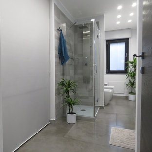 Large modern cloakroom in Catania-Palermo with flat-panel cabinets, white cabinets, a two-piece toilet, multi-coloured tiles, porcelain tiles, grey walls, porcelain flooring, a console sink and grey floors.