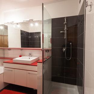 Ispirazione per un bagno di servizio design con ante lisce, ante bianche, pistrelle in bianco e nero, piastrelle in ceramica, pareti multicolore, pavimento con piastrelle in ceramica, lavabo rettangolare, pavimento nero e top rosso