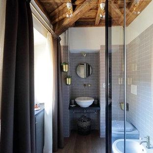 На фото: туалет среднего размера в стиле ретро с плоскими фасадами, черными фасадами, раздельным унитазом, серой плиткой, керамической плиткой, белыми стенами, светлым паркетным полом, настольной раковиной и черной столешницей с