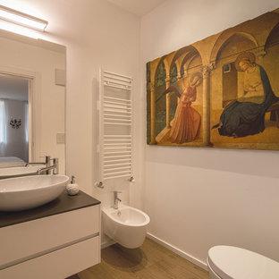 Foto de aseo moderno con armarios con paneles lisos, puertas de armario blancas, bidé, paredes blancas, suelo de madera clara, encimeras grises, lavabo sobreencimera y suelo marrón