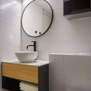 Design ideas for a small modern cloakroom in Milan with grey cabinets, a wall mounted toilet, white tiles, white walls, grey floors, white worktops, flat-panel cabinets and a vessel sink.