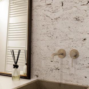Idee per un piccolo bagno di servizio boho chic con ante a filo, ante bianche, WC a due pezzi, piastrelle grigie, pareti grigie, parquet chiaro, lavabo integrato, top in cemento, top bianco, mobile bagno sospeso e carta da parati