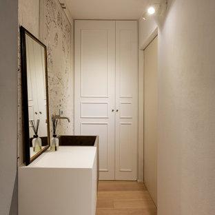 Foto di un piccolo bagno di servizio eclettico con ante a filo, ante bianche, WC a due pezzi, piastrelle grigie, pareti grigie, parquet chiaro, lavabo integrato, top in cemento, top bianco, mobile bagno sospeso e carta da parati