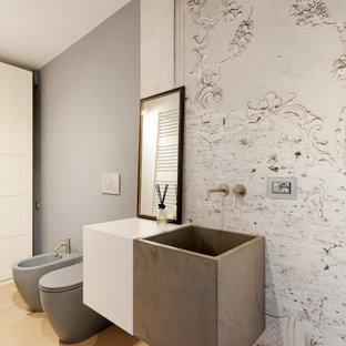 Esempio di un piccolo bagno di servizio bohémian con ante a filo, ante bianche, WC a due pezzi, piastrelle grigie, pareti grigie, parquet chiaro, lavabo integrato, top in cemento, top bianco, mobile bagno sospeso e carta da parati