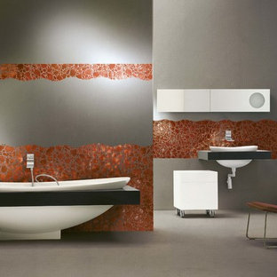 Idée de décoration pour un WC et toilettes design de taille moyenne avec un carrelage rouge, des plaques de verre, béton au sol, des portes de placard blanches, un mur gris, un lavabo intégré, un plan de toilette en verre et un sol gris.