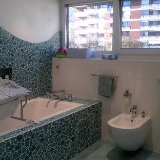Réalisation d'un très grand WC et toilettes design avec des plaques de verre, sol en terrazzo, un sol bleu, des portes de placard bleues, un WC à poser, un carrelage bleu, un mur blanc, une vasque et un plan de toilette en verre.