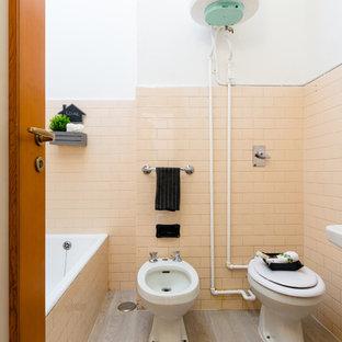 Стильный дизайн: маленький туалет в стиле ретро с биде, розовой плиткой, керамической плиткой, розовыми стенами, полом из ламината, раковиной с пьедесталом и серым полом - последний тренд
