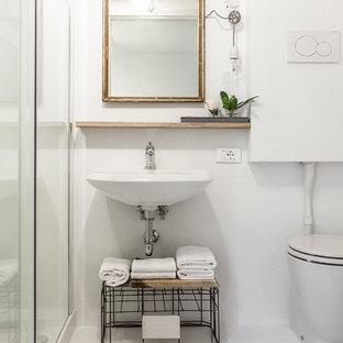 Ispirazione per un bagno di servizio nordico con nessun'anta, WC a due pezzi, pareti bianche, lavabo sospeso e pavimento bianco