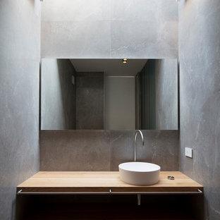 Immagine di un bagno di servizio minimalista di medie dimensioni con nessun'anta, ante in legno chiaro, piastrelle grigie, pareti grigie, lavabo a bacinella e top in legno