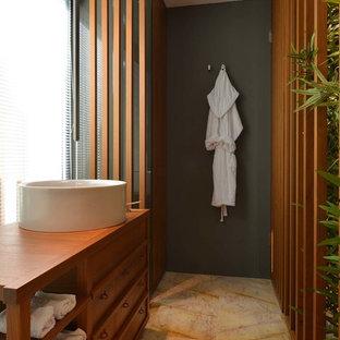 Неиссякаемый источник вдохновения для домашнего уюта: туалет в современном стиле с открытыми фасадами, темными деревянными фасадами, черными стенами, настольной раковиной, столешницей из дерева, желтым полом и коричневой столешницей