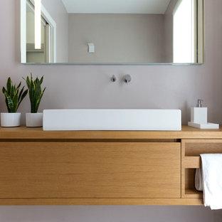 Foto di un bagno di servizio contemporaneo di medie dimensioni con ante in legno chiaro, WC sospeso, pareti beige, lavabo a bacinella, top in legno, pavimento beige e top marrone