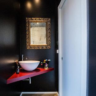 На фото: туалеты в современном стиле с черными стенами, паркетным полом среднего тона и красной столешницей