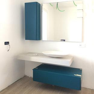 Cette image montre un petit WC et toilettes design avec un placard à porte plane, des portes de placard bleues, un mur blanc, un sol en carrelage de porcelaine, une vasque, un plan de toilette en stratifié, un plan de toilette beige, meuble-lavabo suspendu et un plafond décaissé.