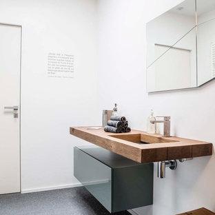 Foto de aseo contemporáneo con armarios con paneles lisos, puertas de armario grises, lavabo de seno grande, encimera de madera y encimeras marrones