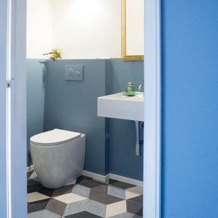 На фото: с невысоким бюджетом маленькие туалеты в современном стиле с синими стенами, полом из керамогранита, подвесной раковиной и разноцветным полом