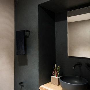 Ispirazione per un bagno di servizio design di medie dimensioni con WC sospeso, piastrelle nere, pareti nere, top in legno e mobile bagno sospeso