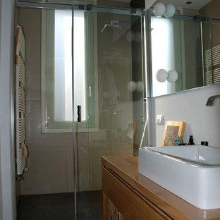 Cette image montre un petit WC et toilettes design avec des portes de placard en bois clair, un WC suspendu, un carrelage blanc, des carreaux de porcelaine, un mur beige, un sol en bois peint, une vasque, un plan de toilette en bois et un sol blanc.