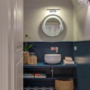 На фото: туалет среднего размера в современном стиле с открытыми фасадами, синими фасадами, синими стенами, полом из цементной плитки, бирюзовым полом и синей столешницей с