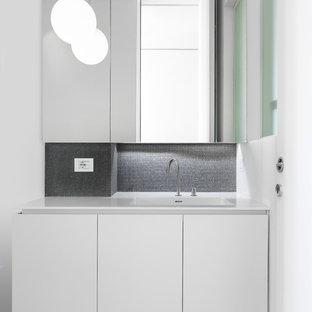 Esempio di un bagno di servizio minimalista di medie dimensioni con ante lisce, ante bianche, WC a due pezzi, piastrelle nere, piastrelle di vetro, pareti nere, pavimento in legno massello medio, lavabo integrato, top in superficie solida e top bianco