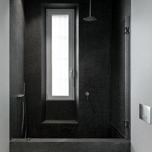 Esempio di un bagno di servizio moderno di medie dimensioni con WC a due pezzi, piastrelle nere, piastrelle di vetro, pareti bianche, pavimento in cemento e pavimento grigio