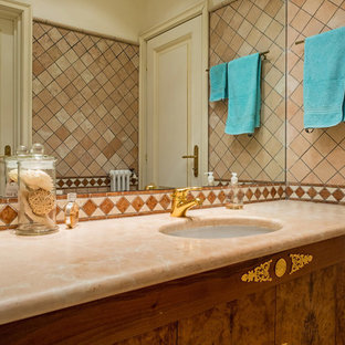 This is an example of a medium sized traditional cloakroom in Milan with medium wood cabinets, brown tiles, ceramic tiles, white walls, a built-in sink and marble worktops.