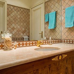 Exemple d'un WC et toilettes chic de taille moyenne avec des portes de placard en bois brun, un carrelage marron, des carreaux de céramique, un mur blanc, un lavabo posé, un plan de toilette en marbre et un plan de toilette rose.