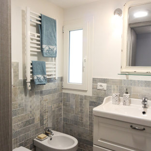This is an example of a small beach style cloakroom in Other with raised-panel cabinets, white cabinets, a two-piece toilet, blue tiles, grey tiles, multi-coloured tiles, porcelain tiles, white walls, porcelain flooring and an integrated sink.