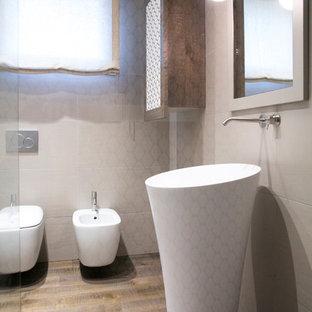 Immagine di un piccolo bagno di servizio minimalista con ante con riquadro incassato, WC a due pezzi, piastrelle in gres porcellanato, parquet scuro e lavabo a colonna