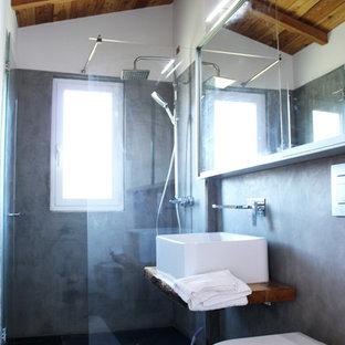 На фото: туалет с раздельным унитазом, черной плиткой, черными стенами, полом из сланца, раковиной с несколькими смесителями и черным полом с