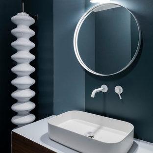 Ispirazione per un bagno di servizio design di medie dimensioni con ante lisce, ante in legno scuro, pareti blu, lavabo a bacinella, top bianco e mobile bagno incassato