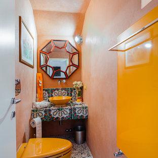 Foto di un bagno di servizio etnico con WC sospeso, pareti arancioni, pavimento con piastrelle a mosaico, lavabo a bacinella, top piastrellato, pavimento multicolore e top multicolore