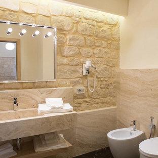 Cette image montre un WC et toilettes minimaliste de taille moyenne avec un WC séparé, un carrelage beige, du carrelage en travertin, un mur beige, un sol en marbre, une grande vasque, un plan de toilette en travertin, un sol noir et un plan de toilette beige.
