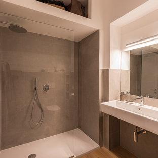 Immagine di un bagno di servizio design di medie dimensioni con WC a due pezzi, piastrelle grigie, piastrelle di cemento, pareti bianche, parquet chiaro, lavabo sospeso, top in legno, pavimento giallo e top giallo