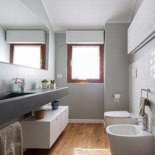 Modelo de aseo actual, pequeño, con armarios con paneles lisos, puertas de armario blancas, bidé, paredes grises, suelo de madera en tonos medios, suelo marrón, baldosas y/o azulejos blancos, lavabo integrado y encimera de cemento