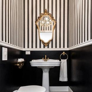 Esempio di un piccolo bagno di servizio classico con WC monopezzo, pavimento in legno massello medio, lavabo a colonna, pavimento marrone e pareti multicolore