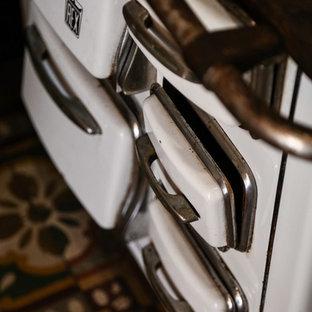 Esempio di un piccolo bagno di servizio shabby-chic style con pareti bianche, pavimento in legno massello medio, pavimento marrone, consolle stile comò, ante con finitura invecchiata, WC monopezzo, piastrelle bianche, piastrelle in metallo, lavabo sospeso, top in acciaio inossidabile e top grigio
