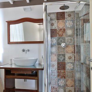 This is an example of a bohemian cloakroom in Other with open cabinets, dark wood cabinets, a wall mounted toilet, multi-coloured tiles, porcelain tiles, white walls, porcelain flooring, a vessel sink, glass worktops, white floors and green worktops.