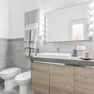 На фото: туалеты в современном стиле с серой плиткой, керамогранитной плиткой, полом из ламината и бежевым полом