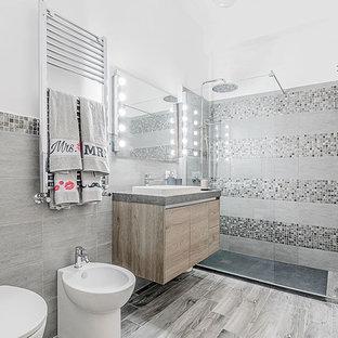 Стильный дизайн: туалет в современном стиле с серой плиткой, керамогранитной плиткой, полом из ламината и бежевым полом - последний тренд