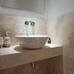 Aménagement d'un petit WC et toilettes contemporain avec un carrelage beige, du carrelage en travertin, un mur blanc, un sol en travertin, une vasque, un plan de toilette en travertin, un sol beige et un plan de toilette beige.