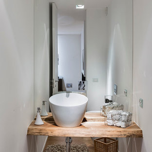 Cette photo montre un WC et toilettes tendance de taille moyenne avec des portes de placard en bois clair, un WC séparé, un carrelage blanc, des carreaux de miroir, un mur blanc, un sol en bois clair, une vasque, un plan de toilette en bois et un plan de toilette marron.