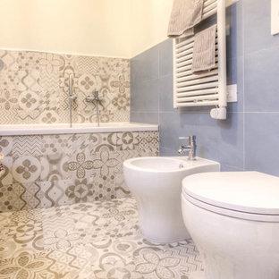 Cette image montre un petit WC et toilettes méditerranéen avec un placard à porte plane, des portes de placard blanches, un WC à poser, un carrelage bleu, des carreaux de porcelaine, un mur blanc, un sol en carrelage de porcelaine, une vasque, un plan de toilette en bois et un sol multicolore.