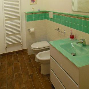 Idée de décoration pour un WC et toilettes champêtre avec des portes de placard blanches, un carrelage multicolore, des carreaux de céramique, un mur multicolore, un sol en carrelage de porcelaine, un plan de toilette en verre et un sol marron.